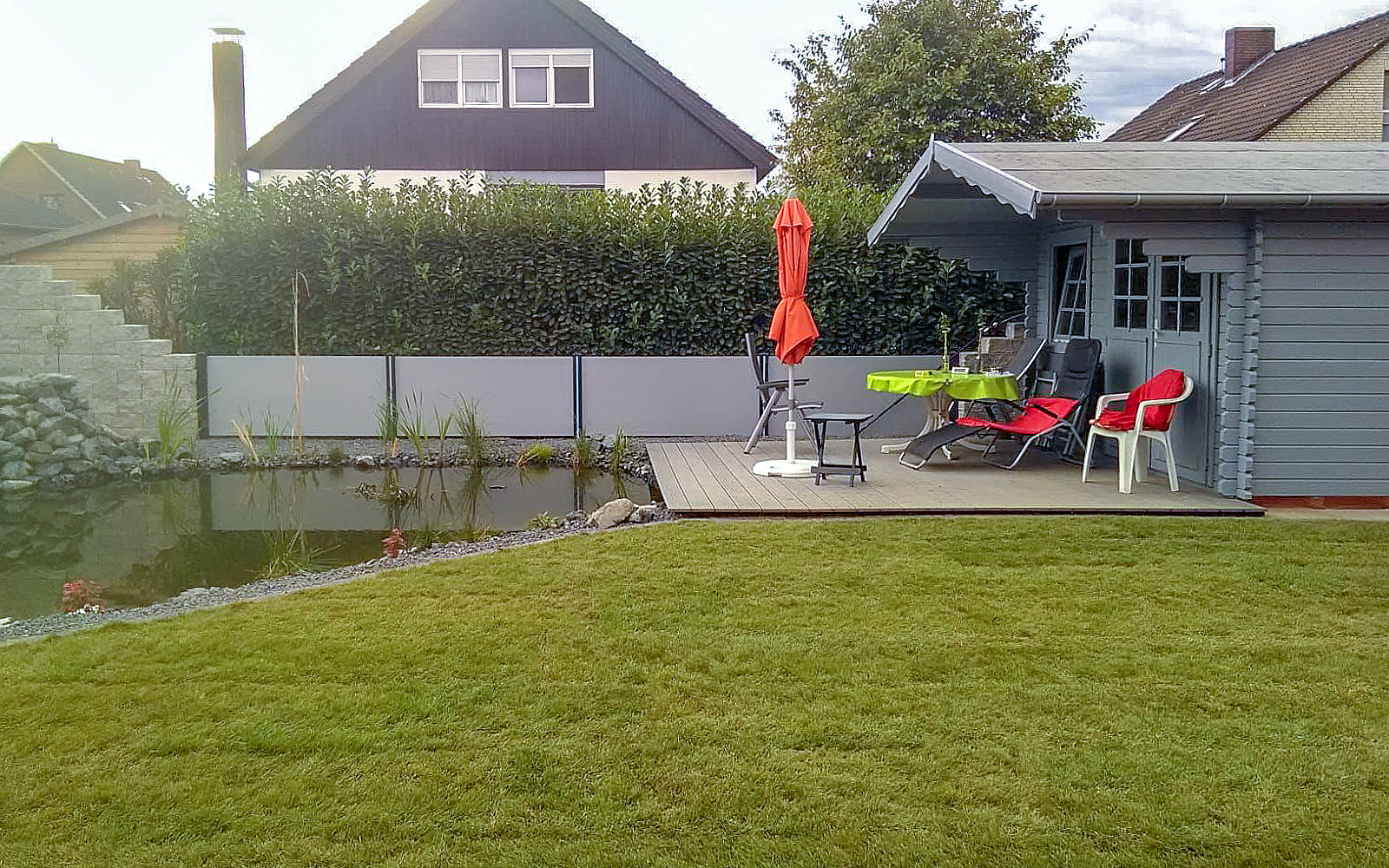 Gartenhaus und WPC Terrasse, Einfassung Aluminiumstecksystem, Mauer aus Betonstein im SChlossmauer-look